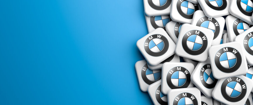 Logos of the car manufacturer BMW on a heap on a table. Copy space. Web banner format.
