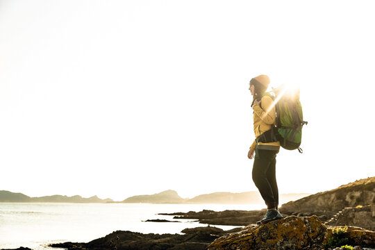 Woman exploring the coastline with backpack