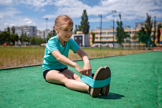 Cute preteen girl making exercises with fitness resistance band at public sportsground in the city, wellness and fitness, sport and recreations, healthy lifestyle