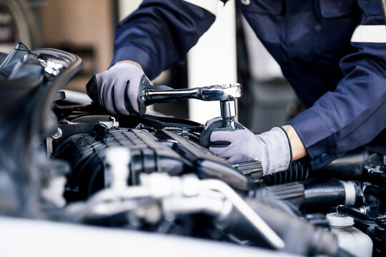 Professional mechanic working on the engine of the car in the garage. Car repair service. The concept of checking the readiness of the car before leaving.
