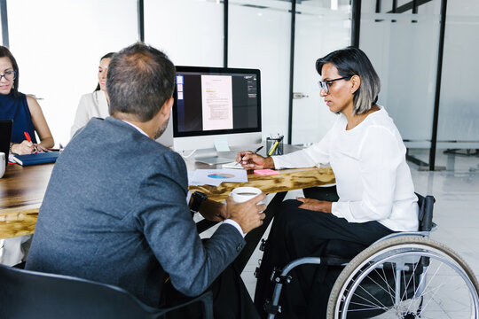 Mexican transgender woman in a wheelchair with a businessman using a smartphone and teamwork in disability concept and disabled people