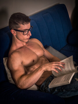 Young male bodybuilder reading book sitting on sofa