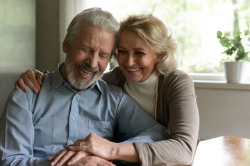 Smiling old middle-aged Caucasian man and woman sit hugging cuddling enjoy happy maturity life together at home. Excited optimistic mature couple spouses show love and care in family relationships.