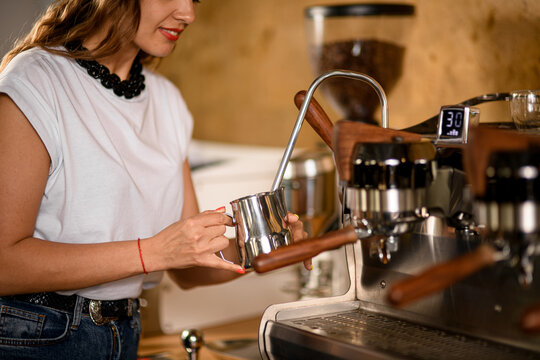 woman barista holds steel jug and makes whipped cream using coffee machine.