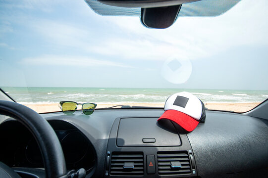 Sea view through the car windshield. Travelling by car to the sea. Cap and sunglasses lie on the car dashboard.