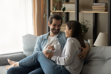 Relaxed happy affectionate young family couple sitting on comfortable couch, holding cups of coffee in hands, enjoying sweet trusted conversation, communicating on weekend in modern living room.