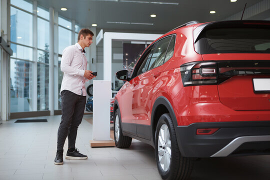 Full length shot of a businessman looking at new SUV car for sale at the dealership