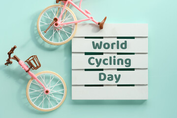 World Cycling Day, Bicycle Day on June 3. Toy model town bike with shadow on mint blue background. Flat lay, top view, minimal retro vintage concept design. Text on wooden palette.