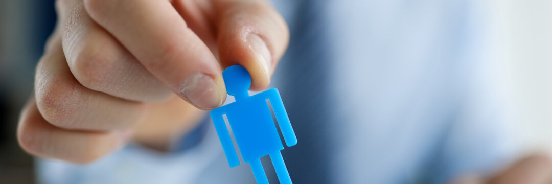 Male hand putting blue toy man to wooden closeup