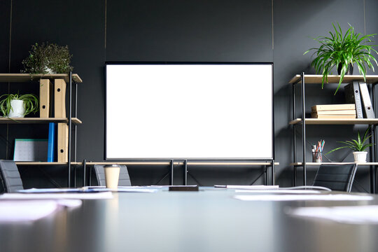 Meeting conference room with blank empty mockup tv screen monitor for advertising standing in modern contemporary office on black wall background. No people. Business technologies concept.