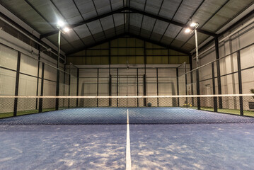 Obraz empty paddle tennis court with lights on in a covered shed with no players - fototapety do salonu