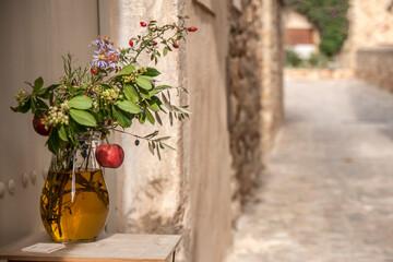 dzbanek z ziołami i owocami w otoczeniu kamiennego, śródziemnomorskiego miasteczka