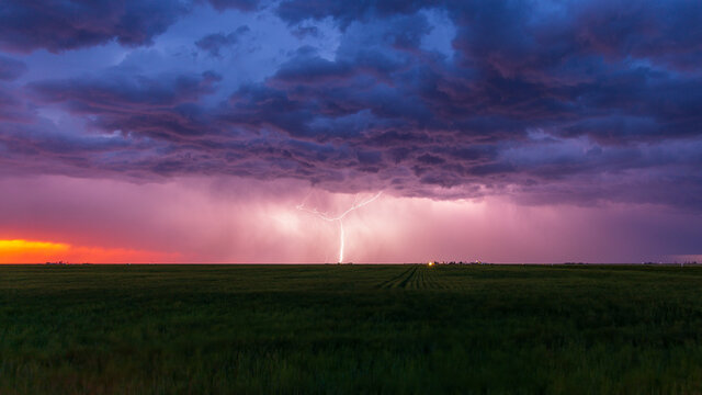 Lightning bolt strikes at dusk on the Wyoming / Colorado border with dark storm clouds overhead