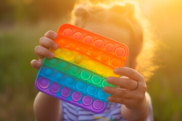 The child plays with a colorful rainbow game of poppit. Silicone fidget close-up.