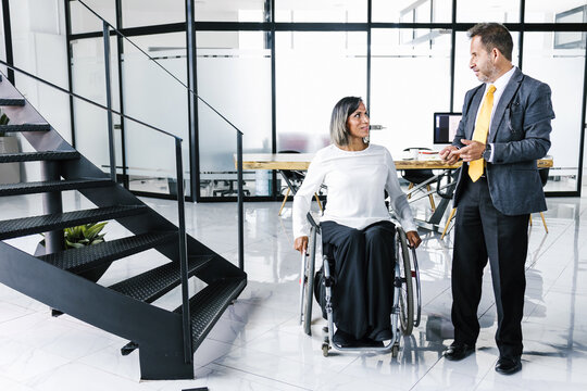 latin disabled transgender businesswoman talking business with colleague at office in Mexico City, in disability concept and disabled people