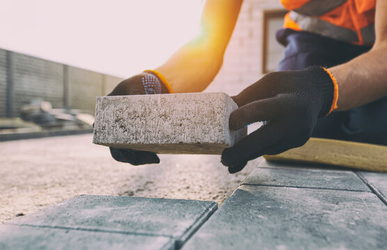 Worker lining paving slabs path