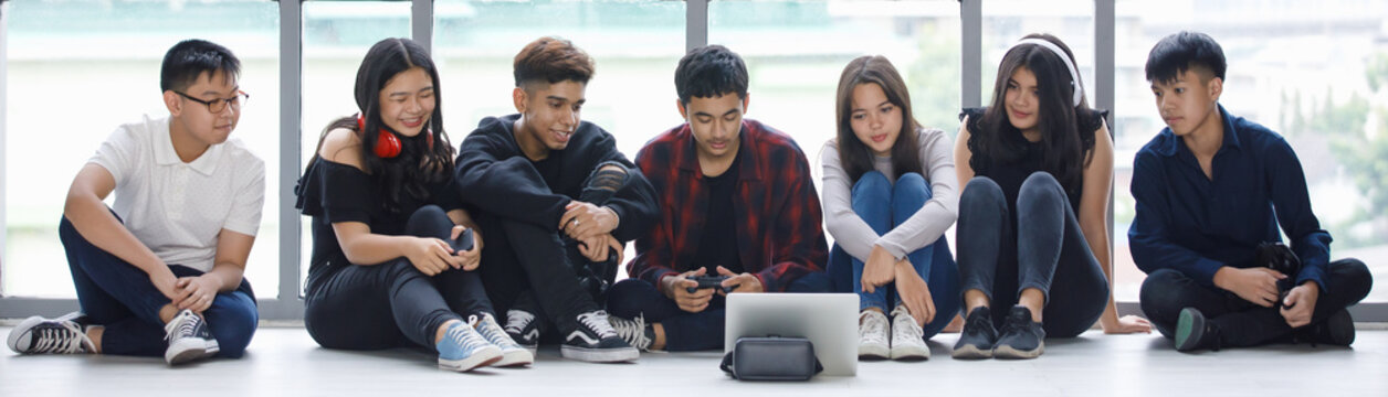 Group of seven young male and female teenagers in casual clothes sitting on the floor and looking at the tablet screen with attractive smiling. College student playing games together with controllers