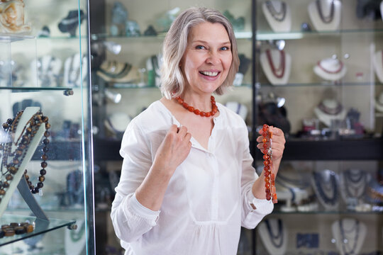 Woman chooses cornelian agate jewelry in boutique. High quality photo