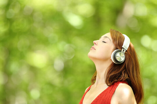 Woman listening to music with headphones breathing