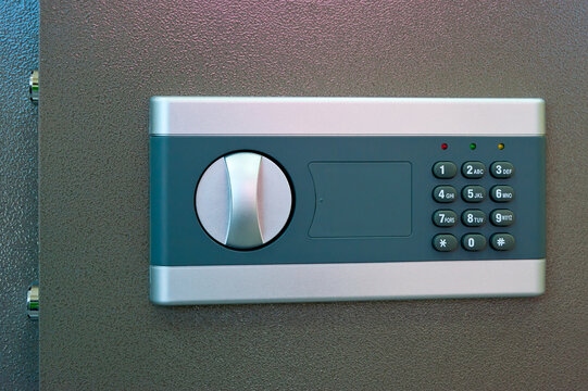A slightly opened safe door with a combination lock.