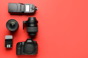 Modern photographer's equipment on color background