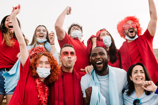Multiracial sports fans in protective face masks screaming while supporting their team at stadium -  Coronavirus spread prevention  and live sports new normality concept