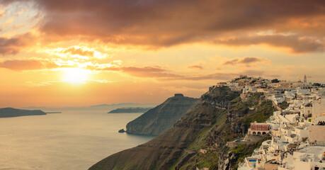 Santorini island, Greece. Fira caldera over Aegean sea, orange color cloudy sky, calm sea