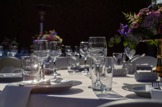 Meticulous outdoor dinner table setting with beautiful flower centerpieces
