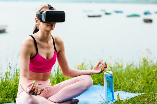 The woman does yoga with virtual glasses outdoors.