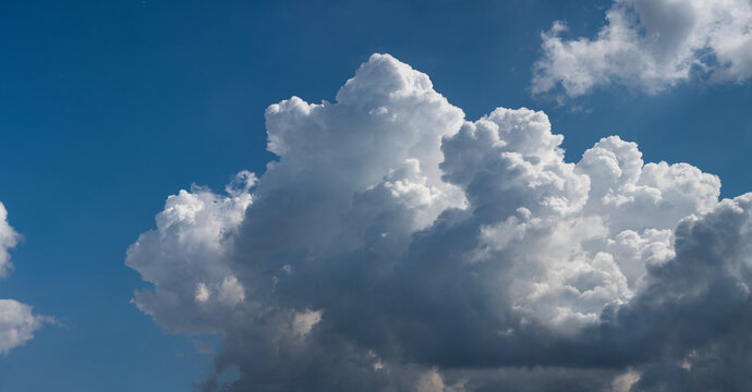 Beautiful cumulus clouds against the blue sky.. Panoramic shot of a cloud cluster. Wide format.