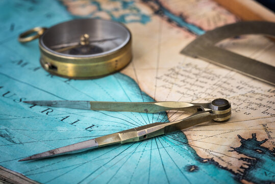 An old geographic map with navigational tools: compass, divider, ruler, protractor. View of the workplace of ship's captain. Travel, geography, navigation, tourism and exploration concept background.