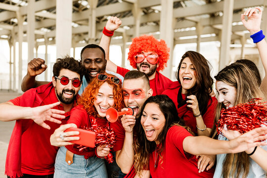 Group of multiracial supporter sport fans taking selfie with mobile phone while supporting their football team - Young people having fun outside the stadium after sport event