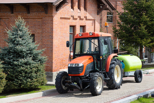 Tractor with Water Tank Trailer in the park on a sunny summer day. Minitractor for lawn watering