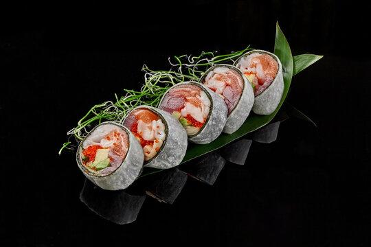 Sushi rolls with tuna, salmon, crab, tobiko and avocado in mamenori