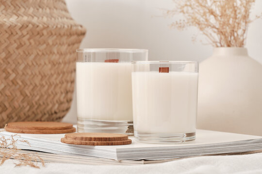 Handmade scented candles in a glass with a wooden lid. Soy wax candles with a wooden wick. Front view.