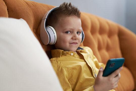 Sweet little boy enjoying some music on big headphones