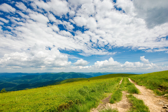 country dirt road through grassy hillside. mountain ridge in the distance beneath a gorgeous cloudscape on the blue sky. travel backcountry concept
