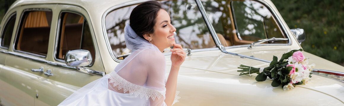 Side view of happy bride standing near wedding bouquet on retro car, banner