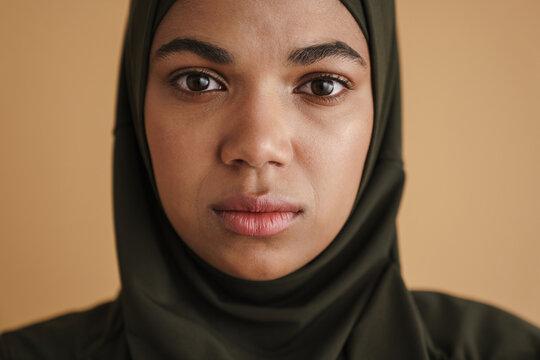 Black muslim woman in hijab posing and looking at camera