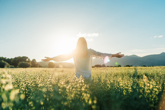 Happy woman showing V sing in countryside field