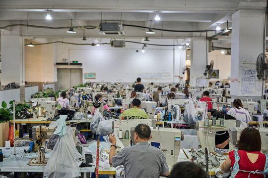 View of busy sewing room in Chinese shoes factory
