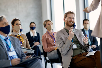 Obraz Happy businessman taking of protective face mask while talking to presenter during seminar. - fototapety do salonu
