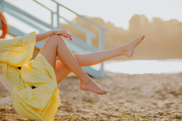 Woman's long slim legs on the sand beach while sunset.