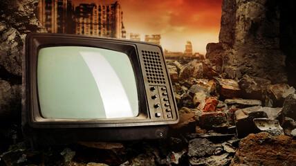 Obraz Photo of old fashioned tv set laying on pile of bricks on ruined city wasteland background. - fototapety do salonu