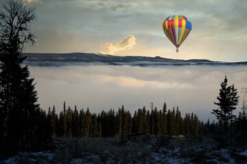 hot air balloon in the sky. The ballon is floating above a sea of fog below in the valley.
