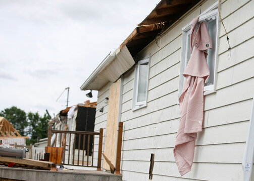 Curtains are seen pulled out a window in the aftermath of a tornado in Mascouche, Quebec