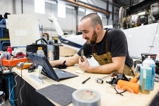 Man working on laptop in helicopter hangar
