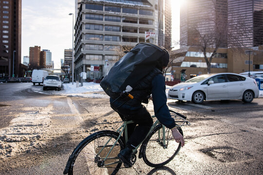Male bike messenger with bag riding bike on sunny winter city street