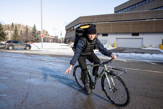 Male bike messenger riding bicycle signaling turn on winter street