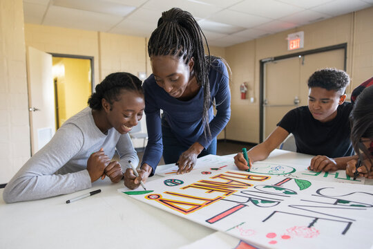 Teen activists drawing environmental posters in community center
